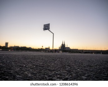 Urban Basketball hoop at sunset with skyline of Cologne, Germany, in background.