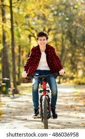 Urban biking - teenage boy riding bike in city park