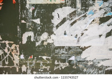Urban billboard wall with torn and ragged glued paper posters and advertisements. For background and texture