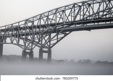 Urban Bridge In Fog Background. The International Blue Water Bridge in heavy fog. The Blue Water Bridges connect Port Huron, Michigan, USA and Sarnia, Ontario in Canada.