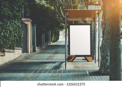 An urban bus stop with blank poster mock-up inside; an informational banner template inside of a stop of city transport on the sidewalk; vertical empty billboard placeholder on the pavement stone