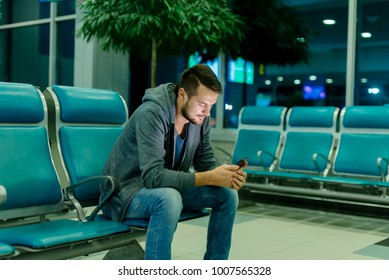 Urban business man talking on smart phone traveling inside in airport. Casual young businessman wearing suit jacket. Handsome male model. Young man with cellphone at the airport while waiting for