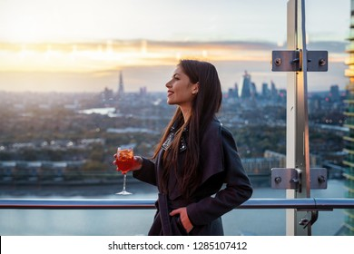Urban business woman relaxes in a rooftop bar in London with a cocktail after work during sunset time, United Kingdom