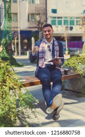 An urban businessman is outdoors and having fun, looking happy with tablet in his hands