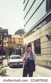 Urban businessman is standing in a beautiful city while drinking coffee and looking at his notebook