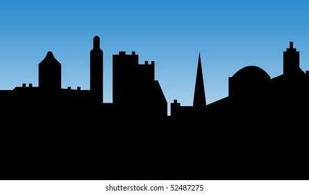 Urban city skyline with cathedral or church, silhouetted with blue sky background.