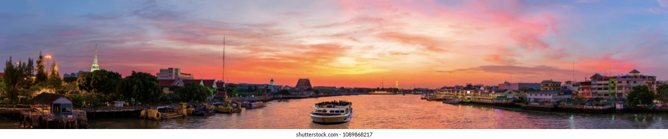 Urban City Skyline, Temple of Dawn (Wat Arun), Wat Kalayanamitr, Santa Cruz Church and Yodpiman River Walk at sunset on Chao Phraya River in Bangkok, Thailand. View from Phra Phuttha Yodfa Bridge.