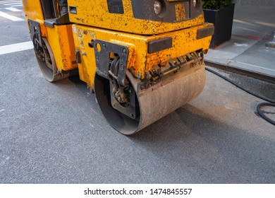 Urban city street black top tarmac patch up work and repairs with a 3 ton asphalt blacktop roller