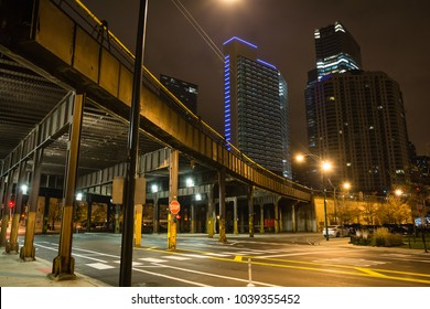 Urban city street corner with vintage train bridge and skyscrapers in Chicago at night