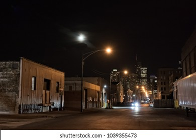 Urban city street with vintage industrial warehouses and the Chicago skyline with the moon at night