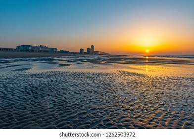 The urban cityscape and beach of Ostend at sunset by the North Sea, West Flanders, Belgium.