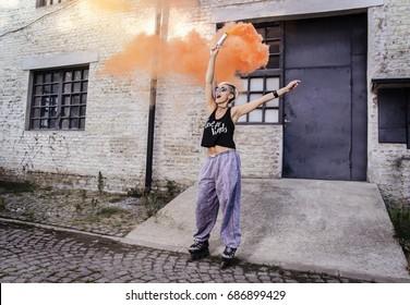 Urban cool young woman wearing roller skates holding orange smoke bomb