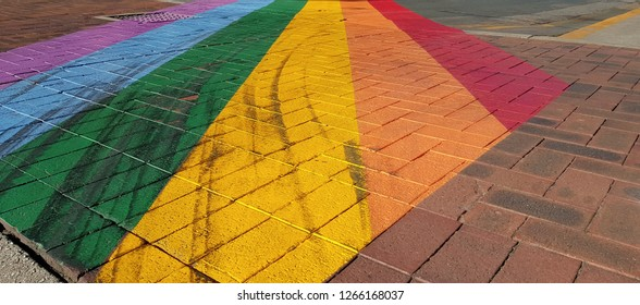 Urban diversity/inclusive concept: A paved city sidewalk painted with rainbow colors.