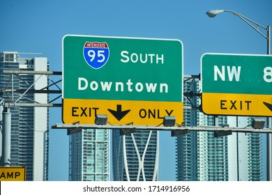 Urban Downtown Miami, Florida green interstate highway sign I-95 southbound financial skyscraper office city view driving from road