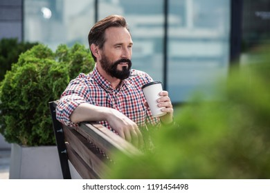 Urban dweller. Nice adult man drinking coffee while enjoying city view