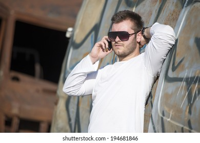 Urban fashion portrait. Good looking. Cool guy. Wearing white shir  and jeans. Standing in front of graffitii wall.