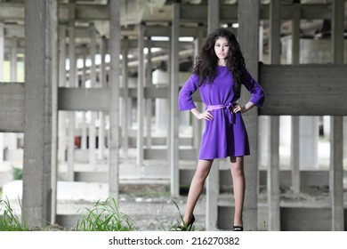 urban fashion portrait of a young asian girl with long curly hair in purple dress and high heels