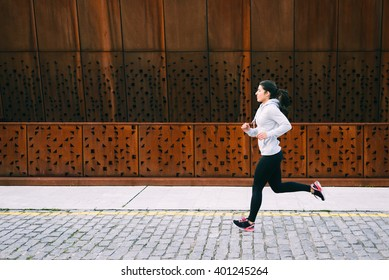 Urban female athlete running. Sporty young woman training outdoor.