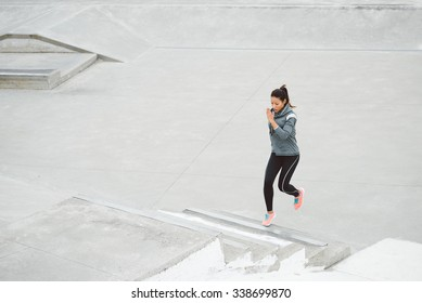 Urban fitness woman running and climbing stairs for legs power and strength training. Female athlete working out outdoor.