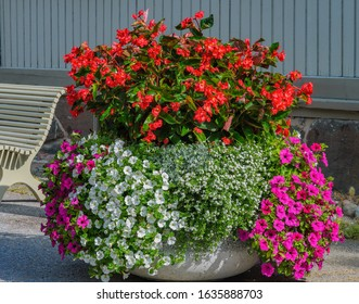 Urban flower pot with different blooming colorful summer flowers stands on the street in Naantali, Finland.