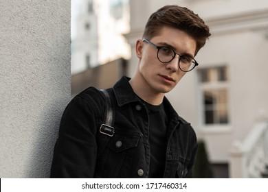 Urban frischen Portrait selbstbewussten jungen Mann mit Frisur in der Mode schwarze denim Jacke in stilvollen Brillen nahe der Wand im Freien. Schönes trendiges Model, das in der Stadt ruht. Gelegentliche Speisekarte. Straße Stil.