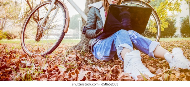 Urban girl with laptop in park. slim hipster woman in jeans using notebook with bicycle sitting on the grass. freelancer using communication technology remote work and eco-friendly  lifestyle.