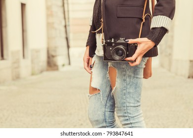 Urban girl with old retro camera posing on the street.