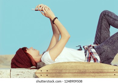 urban girl with a smartphone lying down with a skateboard on her side using phone texting messages and using social media  app