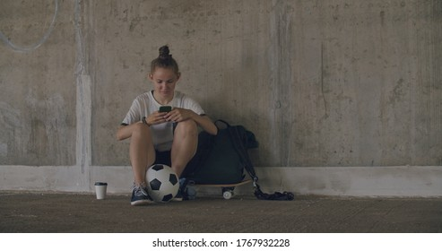 Urban girl using mobile phone. Caucasian teenager football soccer player sitting on skateboard texting on smartphone inside empty covered parking garage. 4K UHD slow motion RAW graded footage