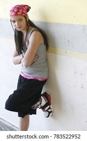Urban girl wearing a pink bandana, arms folded, standing with one foot up against a concrete wall. She looks like she could be a gang member, runaway, or juvenile delinquent looking for trouble.