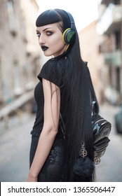 Urban goth girl listening to her favourite music over her big headphones, street in a city surroundings