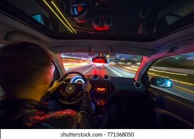 Urban high spees driving on a smal city car with panoramic roof. View from inside car natural light street and other cars is motion blurred.