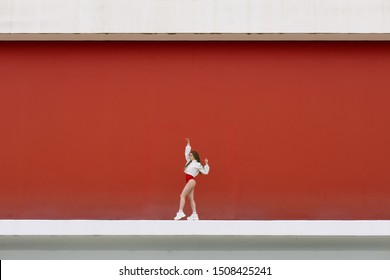 Urban hiphop style girl dancing in the street against yellow wall.