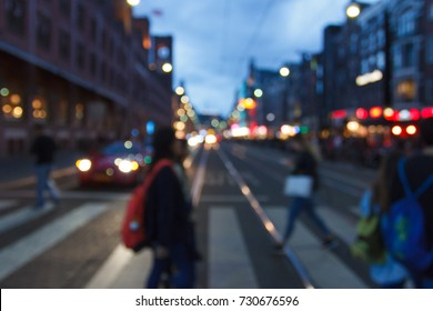 The urban landscape of the city at night with pedestrians out of focus.