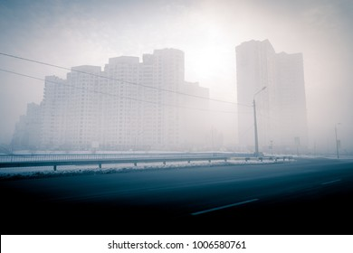 Urban landscape. Foggy winter cityscape. Foggy city street with silhouettes of residential buildings.
