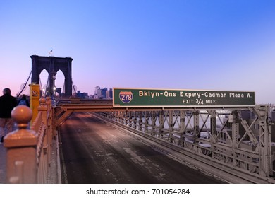 Urban landscape of NYC (USA), One of the pillars of the Brooklyn Bridge viewed from the bridge, with deep green roadsign