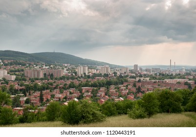 Urban landscape photography of the town Zlin, Czech Republic. Sunlight with cloudy sky above a city surrounded by green trees.