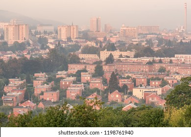 Urban landscape photography of the town Zlin, Czech Republic. Morning side sunlight with fog bringing a mist of a city surrounded by green trees