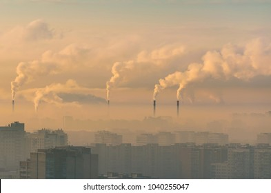 Urban landscape smoked polluted atmosphere from emissions of plants and factories, view of pipes with smoke and residential apartment buildings.