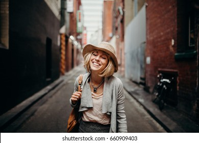 Urban life portrait of smiling woman in the middle of a narrow street.
