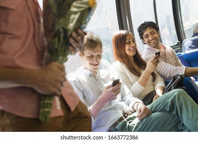 Urban Lifestyle. A group of people, men and women on a city bus, in new york city,. Two people checking their phones. One man standing holding a bunch of flowers.