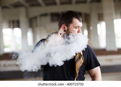 Urban lifestyle portrait of a man vaping in an urban environment with a custom vape mod device.