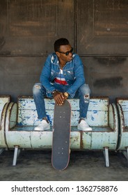 urban lifestyle portrait of young handsome and attractive black afro American skateboarder man sitting on city grunge bench holding skate board posing in cool attitude in beauty and fashion concept
