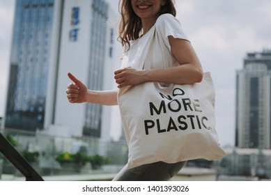 Urban lifestyle and safe environment concept. Cropped head side on portrait of young hipster lady walking around town with eco bag putting thumb up