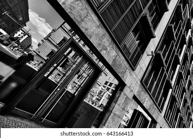 Urban lifestyle view with facade of old building and reflections on glass doors in European city in black and white