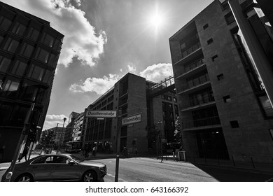 Urban lifestyle view with facades of modern buildings, cloudy sky, car on the road and pillar pointer with plates in European city in black and white