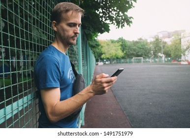 Urban lifestyle. Young bearded man with smartphone and crossbody bag staying near fence of city sport playground.