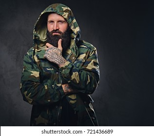Urban look bearded male dressed in a camouflage jacket on grey background.