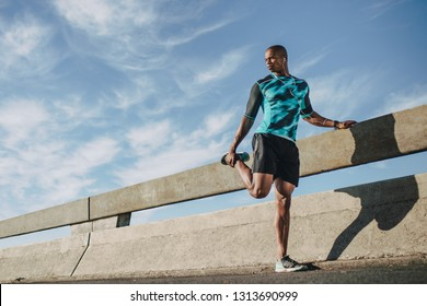 Urban male runner standing by the street and stretching his legs. Young sportsman warming up before a run in morning.