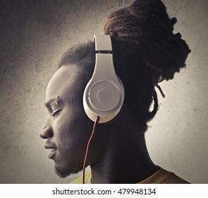 Urban man listening to music through headphones